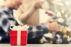 Caja de regalo roja en la tabla con la Navidad de adornamiento de los pares de la falta de definición Imagen de archivo