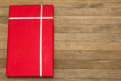 Caja de regalo roja en los tableros de madera Imagen de archivo