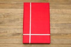Caja de regalo roja en los tableros de madera Fotos de archivo