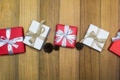 Caja de regalo roja y blanca en la tabla de madera con el cono del pino de la visión superior Imagenes de archivo