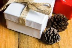 Caja de regalo roja y blanca en la tabla de madera con el cono del pino de la visión superior Fotografía de archivo