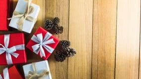 Caja de regalo roja y blanca en la tabla de madera con el cono del pino de la visión superior con el espacio de la copia para el  Foto de archivo