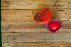 Caja de regalo roja y corazón rojo del cinta y mini dentro en el backgr de madera Imagenes de archivo