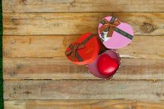 Caja de regalo roja y corazón rojo del cinta y mini dentro en el backgr de madera Imagen de archivo