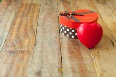 Caja de regalo roja y corazón rojo del cinta y mini dentro en el backgr de madera Fotos de archivo