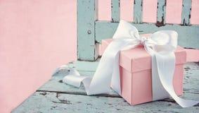 Caja de regalo en una silla de madera azul Imágenes de archivo libres de regalías