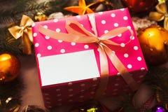 Caja de regalo rosada con la tarjeta en blanco debajo del árbol de navidad Foto de archivo