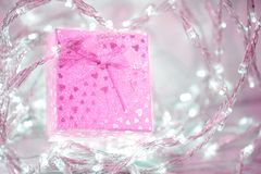 Caja de regalo rosada con un arco y corazones en un fondo borroso de plata imágenes de archivo libres de regalías