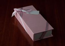 Caja de regalo rosada en fondo de madera brillante Imagen de archivo