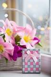 Caja de regalo rosada y ramo blando de tulipanes rosados hermosos en la cesta blanca cerca de la ventana con las gotas de agua en Foto de archivo