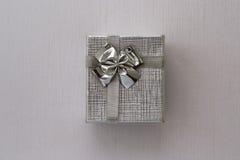 Caja de regalo sobre el fondo de plata Imagenes de archivo