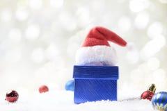 Caja de regalo, sombrero de Papá Noel y bolas de la Navidad en nieve en el CCB abstracto Fotos de archivo libres de regalías