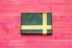 Caja de regalo verde en los tableros de madera Imagen de archivo