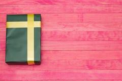 Caja de regalo verde en los tableros de madera rosados Imágenes de archivo libres de regalías