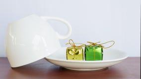 Caja de regalo verde y amarilla y puestos platos y tazas de cristal invertidas Fotografía de archivo