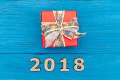 Caja de regalo y Año Nuevo de los números 2018 en la tabla vieja de madera azul Imagen de archivo libre de regalías