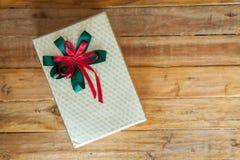 caja de regalo y cinta roja en el fondo de madera con el espacio Imagen de archivo