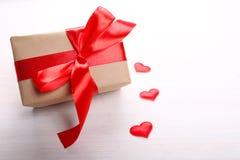 Caja de regalo y corazones rojos en fondo de madera Imagen de archivo