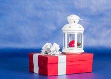 Caja de regalo y linterna, fondo azul Fotos de archivo libres de regalías