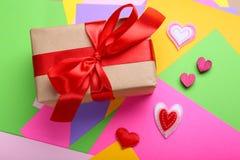 Caja de regalo y pequeños corazones en fondo colorido Imagen de archivo