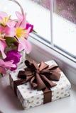 Caja de regalo y ramo blando de tulipanes rosados hermosos en la cesta blanca cerca de la ventana con las gotas de agua en la luz Foto de archivo
