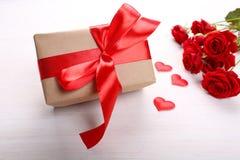 Caja de regalo y rosas rojas en fondo de madera Imagen de archivo libre de regalías