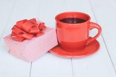 Caja de regalo y taza roja en un fondo de madera ligero Imágenes de archivo libres de regalías