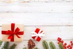 Caja de regalos del regalo de Navidad y elementos rojos del adornamiento en el fondo de madera blanco Imagen de archivo
