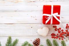 Caja de regalos del regalo de Navidad y elementos rojos del adornamiento en el fondo de madera blanco Imagen de archivo libre de regalías
