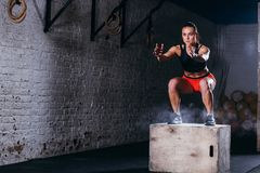 Caja de salto de la mujer Mujer de la aptitud que hace entrenamiento del salto de la caja en el gimnasio apto de la cruz imagen de archivo libre de regalías