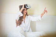 Caja de Vr, mujer asiática que mira sin embargo el dispositivo de VR Imagen de archivo libre de regalías