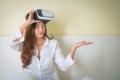 Caja de Vr, mujer asiática que mira sin embargo el dispositivo de VR Imagenes de archivo
