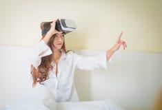 Caja de Vr, mujer asiática que mira sin embargo el dispositivo de VR Fotos de archivo