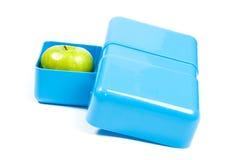 Caja del almuerzo azul con una manzana verde Imágenes de archivo libres de regalías