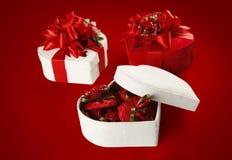 Caja del chocolate del día y de la Navidad de la tarjeta del día de San Valentín (en fondo rojo). Foto de archivo libre de regalías