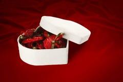 Caja del chocolate del día y de la Navidad de la tarjeta del día de San Valentín (en fondo rojo). Imagen de archivo libre de regalías