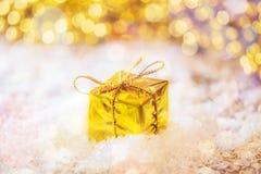 Caja del oro de la Navidad en la nieve con la luz del fondo en la tabla de madera ornamentos de oro y blancos Foto de archivo