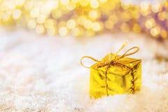 Caja del oro de la Navidad en la nieve con la luz del fondo ornamentos de oro y blancos Fotos de archivo libres de regalías