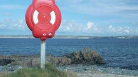 Caja del salvavidas en la bahía de la orilla Orilla rocosa almacen de video