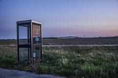 Caja del teléfono en paisaje rural en la puesta del sol Imagenes de archivo