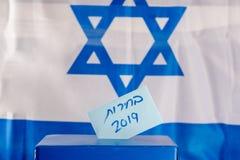 Caja del voto Elecciones hebreas 2019 del texto en el papel de votación sobre fondo de la bandera de Israel fotos de archivo