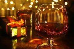 Caja del whisky, del coñac, del brandy y de regalo en la tabla de madera Composición de la celebración en el fondo ligero Foto de archivo