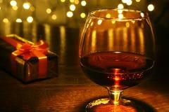 Caja del whisky, del coñac, del brandy y de regalo en la tabla de madera Composición de la celebración en el fondo ligero Fotografía de archivo