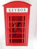 Caja dominante de la forma roja de la casa en el fondo blanco Imagen de archivo libre de regalías
