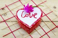 Caja en forma de corazón adornada con una flor rosada Fotos de archivo libres de regalías