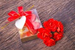 Caja en forma de corazón de los chocolates con la tarjeta en blanco y las rosas Imágenes de archivo libres de regalías