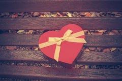 Caja en forma de corazón en banco de parque Imagen de archivo