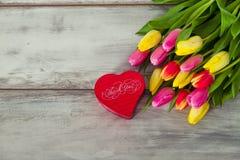 Caja en la forma de corazón y de tulipanes Imágenes de archivo libres de regalías