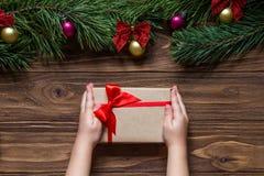 Caja en las manos del ` s del niño, macro del regalo de Navidad Tema agradable de la Navidad en el fondo de madera con las ramas  Foto de archivo