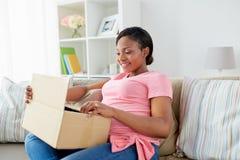 Caja feliz del paquete de la abertura de la mujer embarazada en casa fotos de archivo